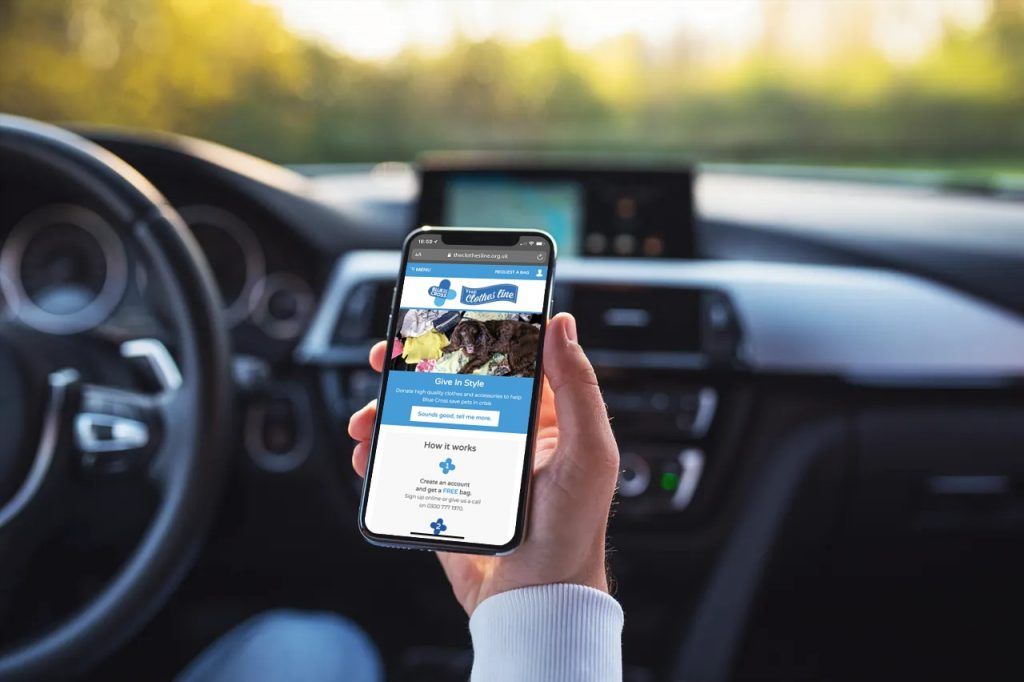 Man viewing Blue Cross on smartphone in car